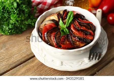 Ratatouille in bowl, on wooden table background - stock photo