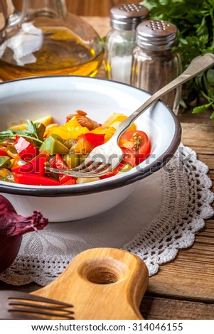 Ratatouille made of eggplant, zucchini, bell pepper and tomato and seasoned with herbs. Selective focus. - stock photo