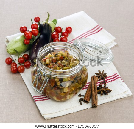ratatouille of vegetables in a glass jar with vegetables in the background with spices - stock photo