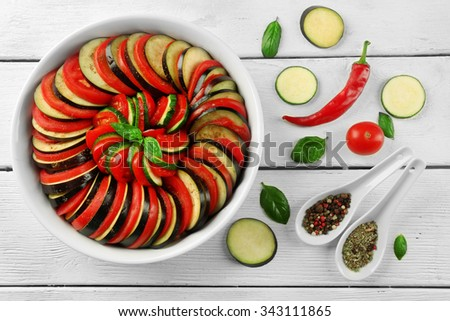 Ratatouille, stewed vegetable dish with tomatoes, zucchini, eggplant before cooking in pan, on wooden background - stock photo