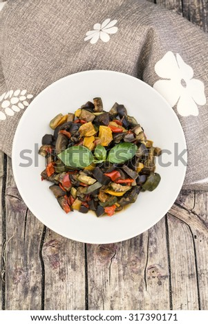 Ratatouille with eggplant, zucchini, red and yellow peppers on wooden background - stock photo