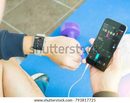 Ratchaburi,Thailand ,19 Aug 2017 : Man Comparing Activity App and check on Apple Watch and iPhone After Working out