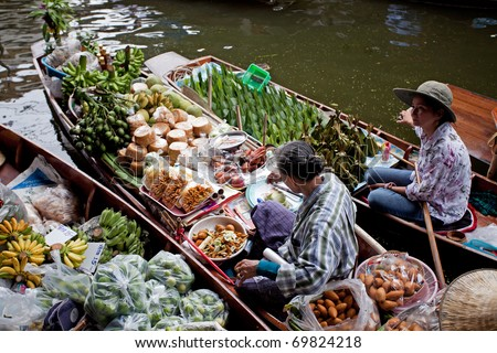 RATCHABURI, THAILAND - AUGUST 28: Food boats at Damnoen Saduak floating market on August 28, 2010 in Ratchaburi, Thailand. Damnoen Saduak is a very popular tourist attraction in Thailand. - stock photo