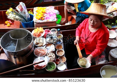 RATCHABURI, THAILAND - FEB 13: A woman makes Thai food at Damnoen Saduak floating market on February 13, 2011 in Ratchaburi, Thailand. Its popular for traditional style Thai food and old Thai culture.