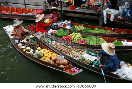 RATCHABURI, THAILAND - JULY 5: Fruit boats at Damnoen Saduak floating market on July 5, 2009 in Ratchaburi, Thailand. Damnoen Saduak is a very popular tourist attraction in Thailand. - stock photo