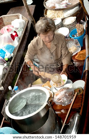 RATCHABURI,THAILAND - JULY 21: Thai female Thai vendor is sitting in her boat and grill kitchen in Damnoen Saduak floating market on July 21,2013 at Ratchaburi Province,Middle of Thailand.