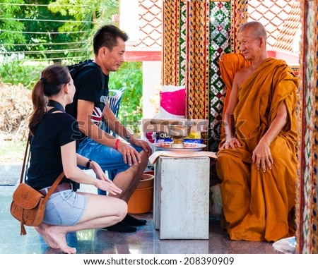 Ratchaburi, Thailand - May 24, 2014: Buddist monk blesses religious people at the temple from Damnoen Saduak Floating Market, Thailand.Buddhism is the primary religion in Thailand.