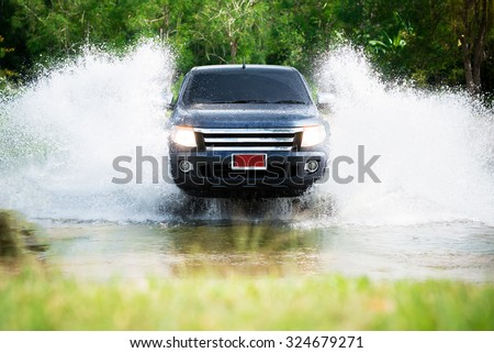 Ratchaburi, Thailand - Nov 4, 2014 : 4WD car wades river in suanphueng  - stock photo