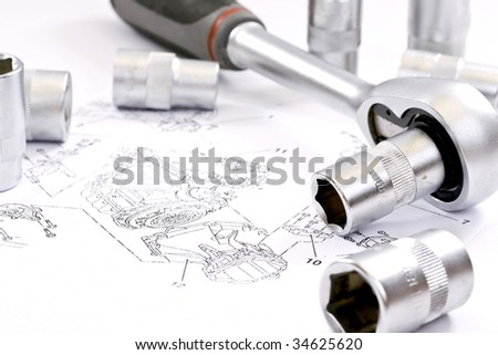 Ratchet spanner and sockets on technical draw background - stock photo