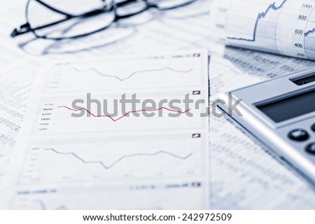 Rate tables and diagrams symbolize the volatility of the financial market. - stock photo