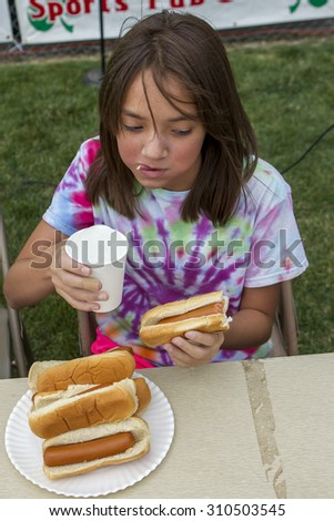 Rathdrum, Idaho USA - August 15, 2015. A girl participates in a hot dog eating contest during Taste of Rathdrum, Idaho USA August 15, 2015. - stock photo