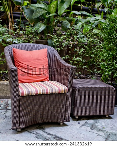 Rattan chair and rattan coffee table with green trees at outdoor - stock photo
