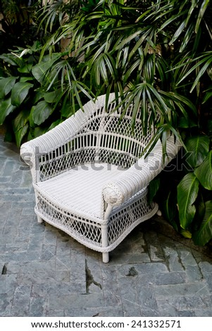 Rattan chair with green trees at outdoor - stock photo