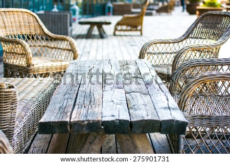 Rattan chairs and empty wooden table on terrace - stock photo