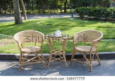 Rattan chairs and table in empty cafe - stock photo