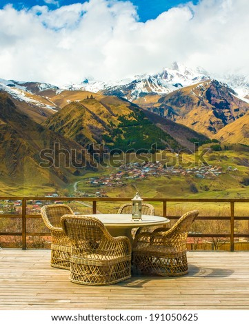 Rattan chairs and table on terrace with beautiful mountain view - stock photo
