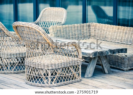 Rattan chairs and wooden table on terrace. Toned image - stock photo