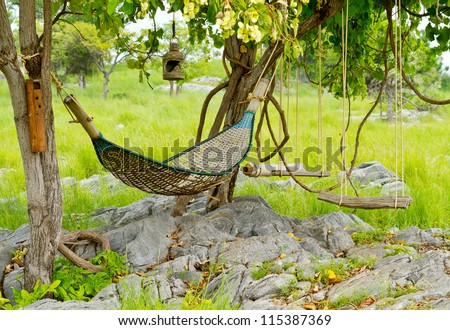rattan hammock hanging on tree in green garden - stock photo