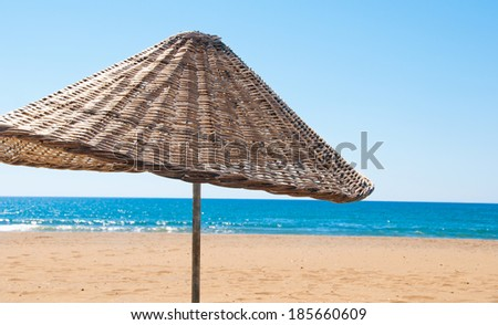 Rattan parasol of wicker at the seaside. - stock photo