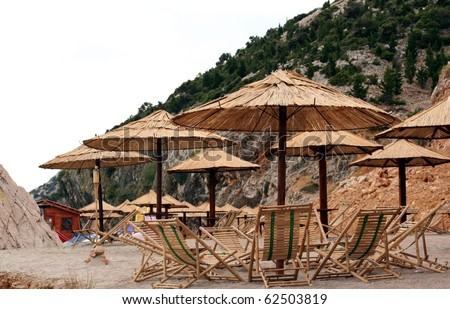 Rattan Umbrellas and Lounges on a Croatian sand beach - stock photo