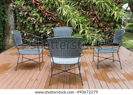 rattan wicker chair and desk on patio beside garden in rainy day