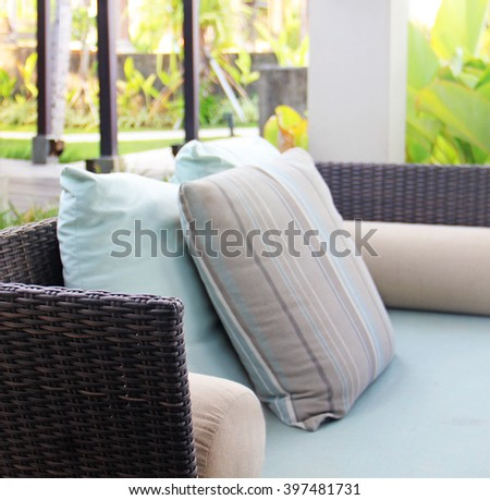 rattan wicker sofa with pillows - stock photo