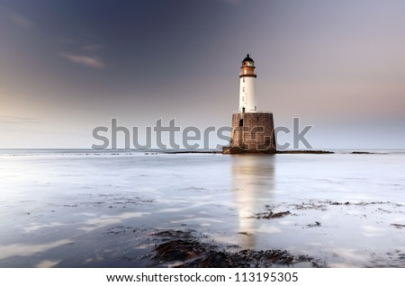 Rattray head lighthouse on the north east coast of Scotland as the Sun setting with the tide coming in. - stock photo