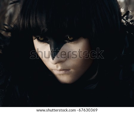 raven girl with short black hair. around the neck of her black feathers. Facial face art that makes her look like a crow. her back the sun is shining, but the street is still cold