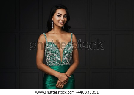 raven haired indian lady posing in studio against gray wall