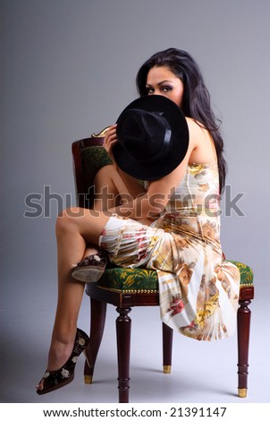 raven haired woman with hat hiding her face