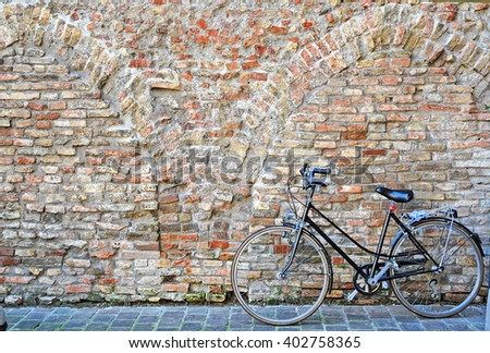 Ravenna, bicycle parked against an old wall in the city center.