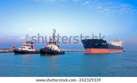 Ravenna, Italy - JANUARY 07, 2015: Tugboat ESPADA and EDUARDO pulling JIA DA to assist the ship from the dock at the Marina di Ravenna - stock photo