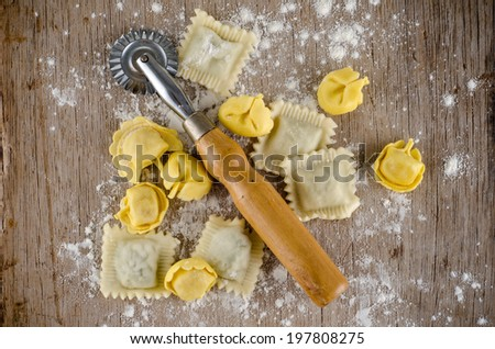 Ravioli and tortellini with pasta cutter on a wood - stock photo