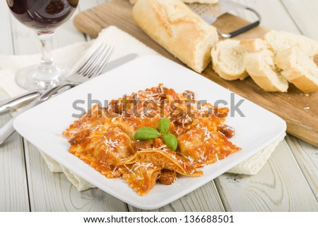 Ravioli - Italian egg pasta with chicken and chorizo filling with creamy tomato and chorizo butter sauce.  Garnished with parmigiano-reggiano. Crusty bread, parmesan and red wine on background. - stock photo