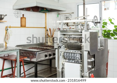 Ravioli pasta machine by stove in commercial kitchen - stock photo
