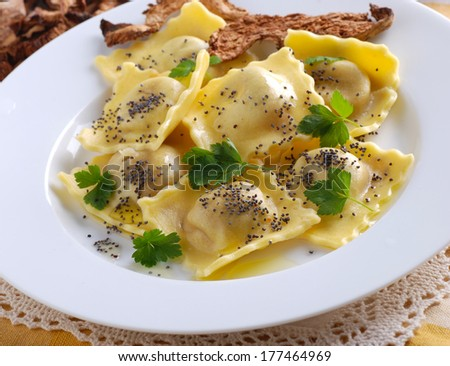 ravioli stuffed with mushrooms garnished with poppy seeds and parsley - stock photo