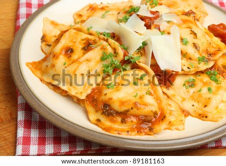 Ravioli with a tomato sauce and Parmesan cheese shavings. - stock photo