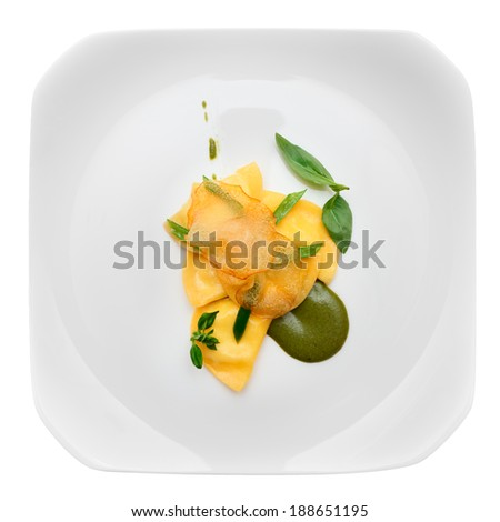 Ravioli with pesto sauce and potato chips in plate, isolated on white - stock photo