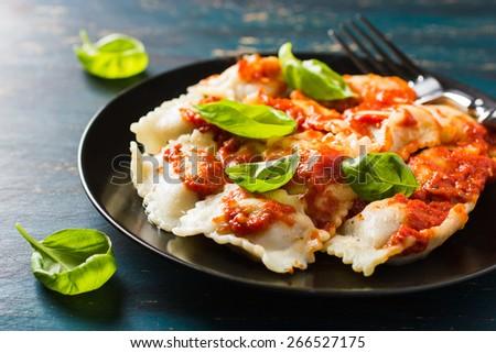 Ravioli with tomato sauce and basil on dark background - stock photo