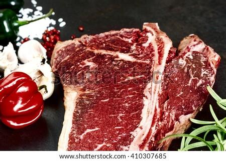 Raw aged meat T-bone steak and seasoning on dark background - stock photo