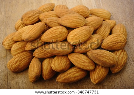 raw almonds on wooden background - stock photo