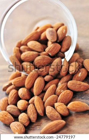 Raw almonds spilling out of small glass bowl - stock photo