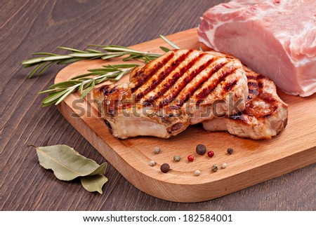 Raw and grilled meat  with spices on a  wooden board - stock photo