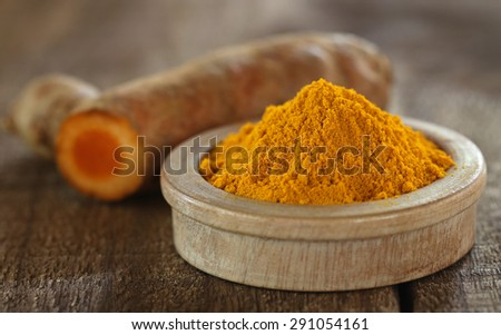 Raw and ground turmeric on wooden surface