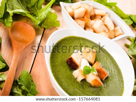 Raw and prepared spinach soup on the wooden table. Selective focus on the spinach soup - stock photo