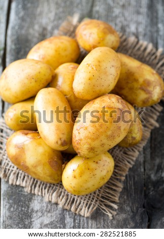 raw baby potatoes on wooden surface - stock photo