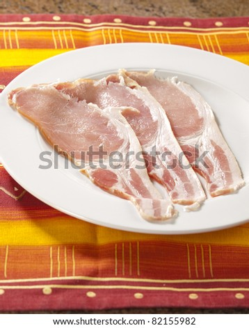 Raw bacon slices on a white plate, set on a warm coloured placemat - stock photo