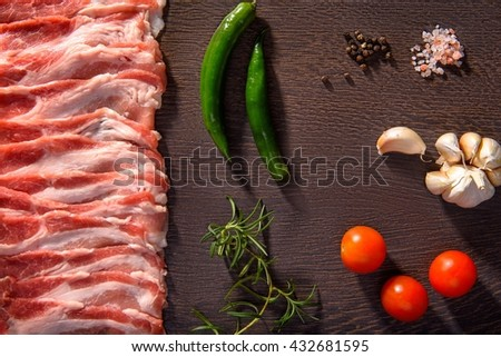 Raw bacon slices on with vegetables on a wooden background.  - stock photo