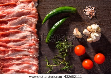 Raw bacon slices with vegetables. Top view - stock photo