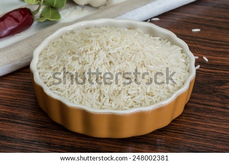 Raw Basmati rice in the bowl on wooden background